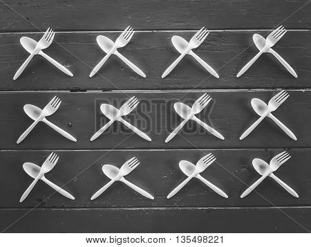 plastic forks and plastic spoons in black and white