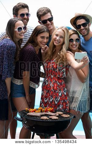 Group of friends taking a selfie while preparing barbecue near pool