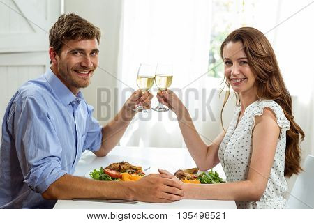 Portrait of happy couple toasting wineglasses while having lunch at home