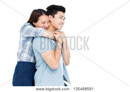 Happy young couple embracing on white background