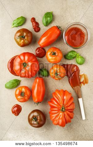Assortment of fresh French heirloom tomatoes, basil and tomato ketchup on natural stone surface