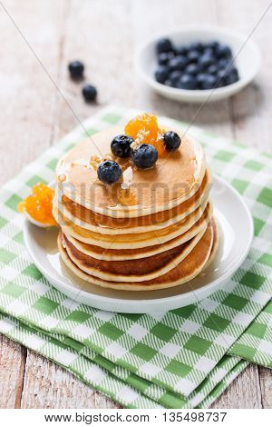 Homemade sweet pancakes with blueberries, fruit jam and honey on a white plate, closeup