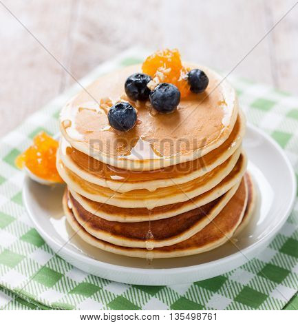 Homemade sweet pancakes with blueberries, fruit jam and honey on a white plate