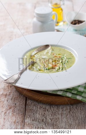 Zucchini vegetable creamy soup puree in a bowl on a wooden background