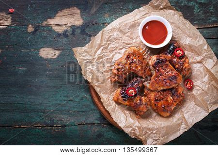 Roasted barbecue chicken wings with bbq sauce italian herbs olive oil and pepper top view with copy space