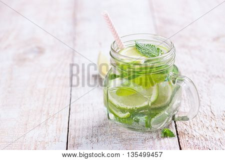 Tasty colorful drink with cold green tea mint and cucumber in a glass jar on a vintage background closeup