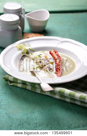 Zucchini cream soup with red pepper cream spices and balsamic cream on a wooden background