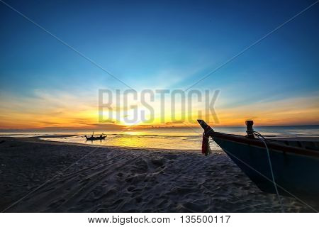 beautiful sunset sunrise background on the beach with silhouette boat in the foreground