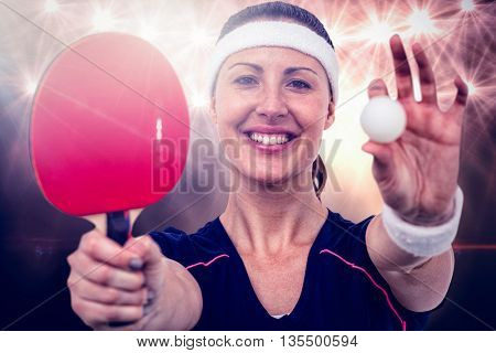 Composite image of female athlete holding table tennis paddle and ball against spotlight