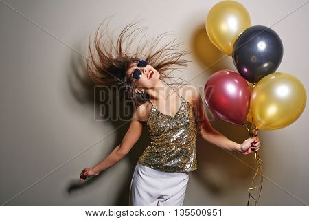 Portrait of young woman hanging out with balloons