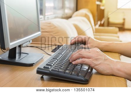 Male hands typing on full size keyboard in front of a monitor in a brightly lit room with large window in the background selective focus on keyboard and closer hand