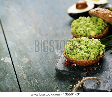 Tasty avocado sandwiches on slate background