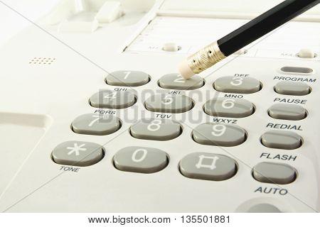 One pencil pressing key on a phone