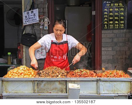 Wuhan, China - June 22, 2015:woman is selling snacks outdoor in Wuhan, China