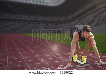 Composite image of sportsman waiting on the starting block in a stadium