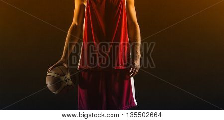 Portrait of basketball player holding a ball on a gym