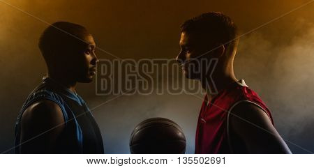 Two basketball player looking each other with a basketball between them