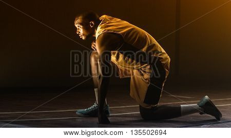 Basketball player preparing to play with knee on the floor and looking up on a gym