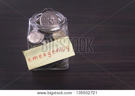 Finacial concept. Money in the glass on wooden table with emergency word and copy space area.