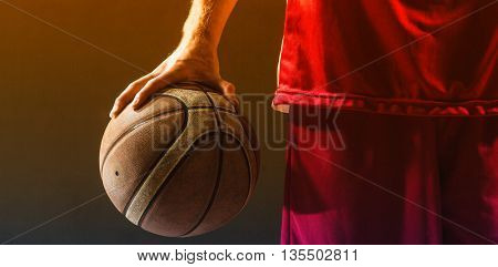 Close up on a basketball held by basketball player on a gym