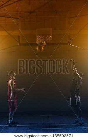 Two basketball player in a gymnasium with one scoring a shoot against a black background