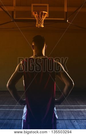 Basketball player with his hands on his hips looking the basketball hoop