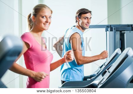 Happy couple is exercising in gym. They are running on treadmill.