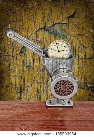 Alarm clock in meat grinder on grunge scratched background.Toned image.