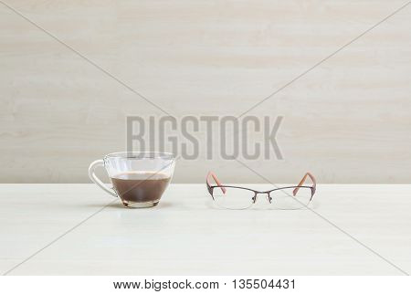 Closeup black coffee in transparent cup of coffee with eyeglasses on blurred wooden desk and wall textured background in the meeting room under window light