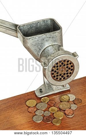 Meat grinder and coins on wooden table and white background.Financial concept.