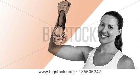 Female athlete posing with gold medals after victory against colored background