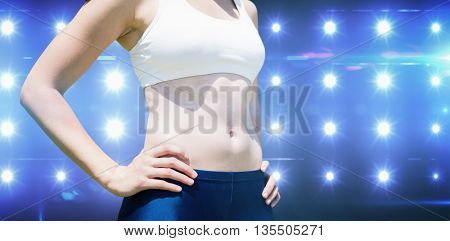 Portrait of sportswoman chest is posing with hands on hips against composite image of blue spotlight