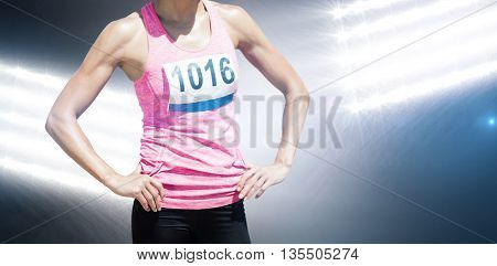 Portrait of sportswoman chest is posing with hands on hips against spotlights