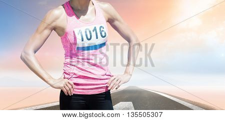 Portrait of sportswoman chest is posing with hands on hips against road landscape