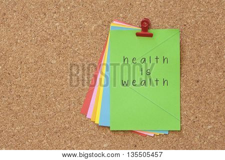 health is wealth written on color sticker notes over cork board background