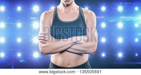 Athlete posing with arms crossed against composite image of blue spotlight