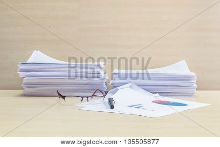 Closeup pile of work paper glasses and pen on blurred wooden desk and wall textured background in the meeting room under window light hard work concept