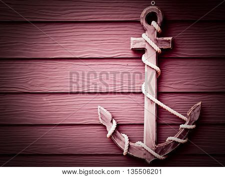 close up red oak wooden anchor on wall vintage background vignette