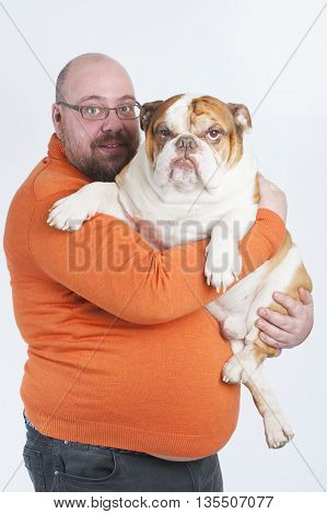 The man is holding an English bulldog. Studio photography on a white background (light).