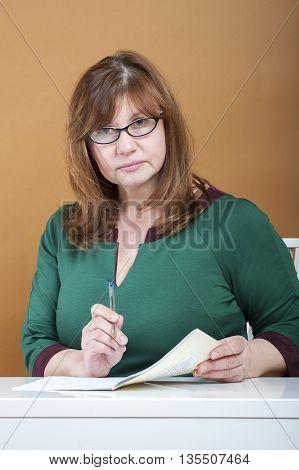 Woman Teacher Checks School Notebooks..