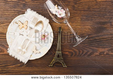 Tableware and silverware with miniaturized Eiffel tower on the wooden background