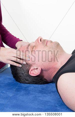Mature Male Receiving Ear Reflexology Massage Of Both Temples