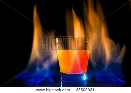 Alcoholic fruit cocktail surrounded by flames on black background