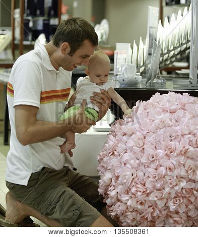 Family Shopping. Young Father And His Daughter In The Mall. He Shows A Huge Floral Bouquet