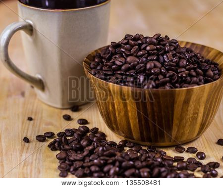 Wooden bowl full of dark coffee beans in foreground with coffee mug in back. Shallow depth of field.