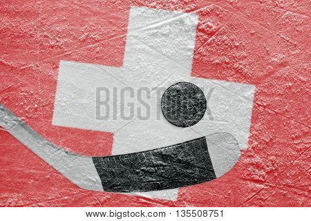 The image of the Swiss flag and hockey puck with the stick on the ice. Concept