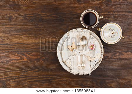 Tableware and silverware with cup of coffee on the wooden background