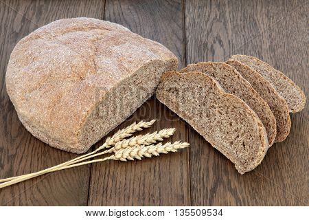 Rustic homemade brown bread loaf with slices and wheat sheaths over oak wood background.