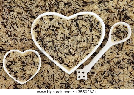 Long grain wild rice in heart shaped porcelain dishes and spoon forming an abstract background.