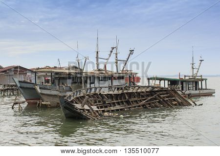 SANDAKAN, MALAYSIA - 23 JUNE 2016: Fishing boats with one sunk due to bad weather. Climate change and rising sea levels environmental problem.